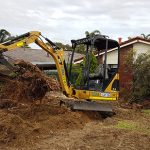 A mini excavator working hard with wood and dirt.
