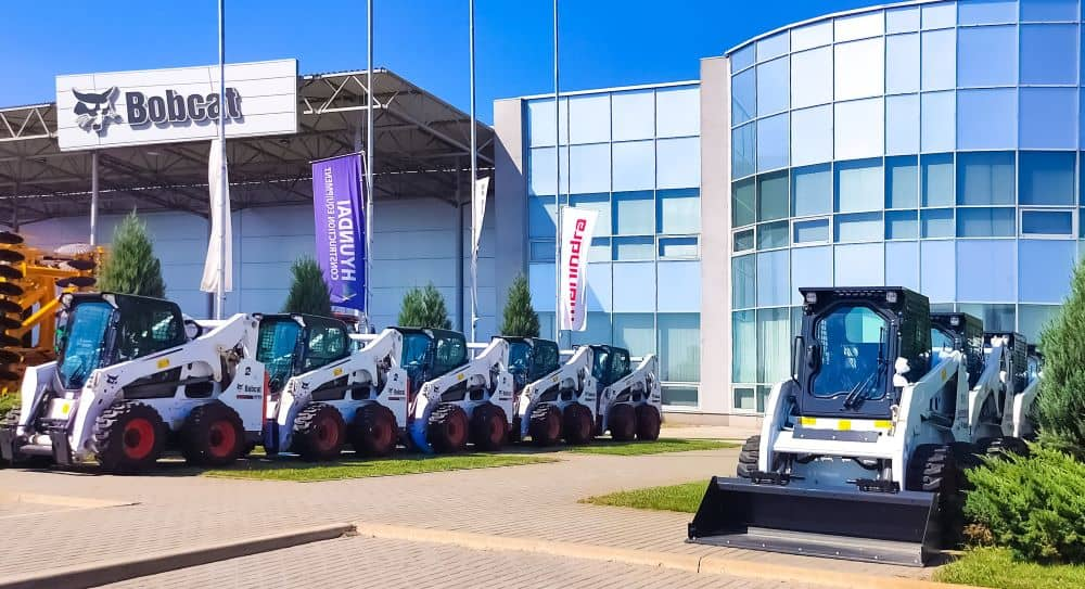 Bobcat skid steers lined outside heavy equipment supplier.