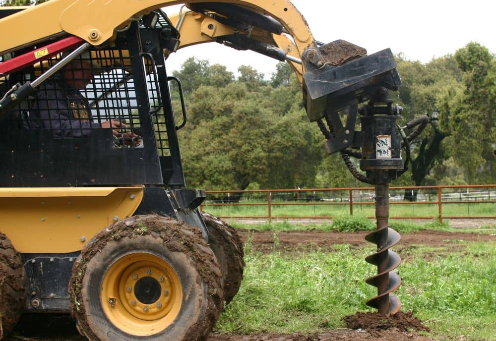 Skid Steer with auger attachment digging a hole in the ground